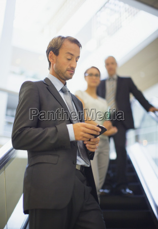 businessman using cell phone on escalator