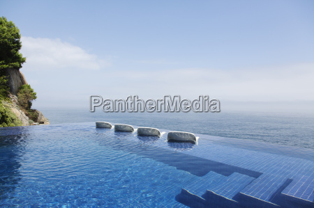 lounge chairs in infinity pool overlooking