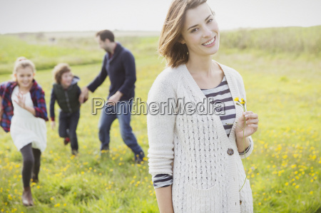 portrait smiling woman holding wildflower in