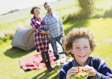 portrait smiling boy eating hamburger with