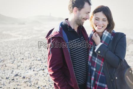 smiling brunette couple standing on sunny