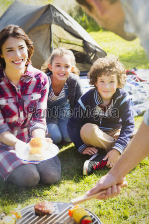 family watching father barbecuing at campsite