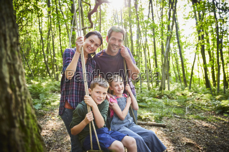 portrait smiling family at rope swing