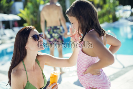 mother applying suntan lotion on daughters