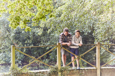 father and son on footbridge in
