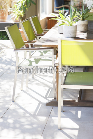 chairs and table with potted plants
