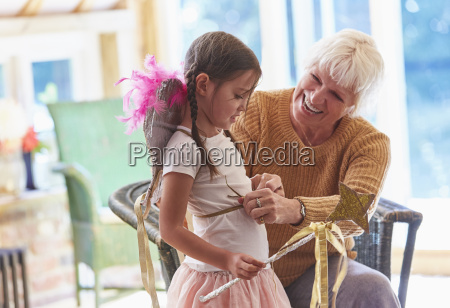 grandmother fitting granddaughter with wings