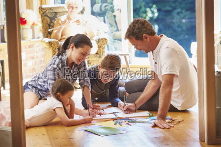 family drawing and coloring on floor