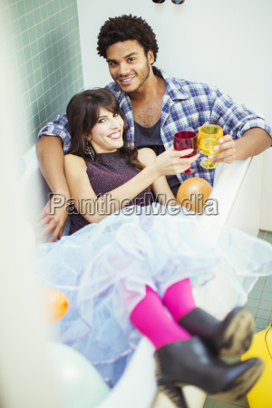 couple toasting each other in bathtub