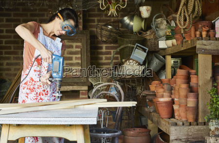 woman using power sander in workshop