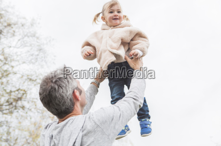 father lifting toddler daughter overhead
