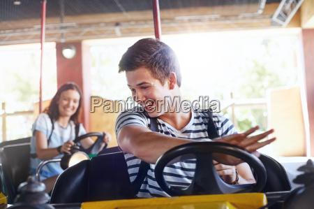 smiling young man riding bumper cars