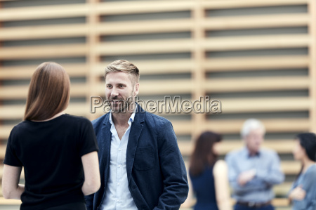 businessman and businesswoman talking in lobby