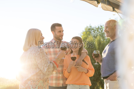 family talking and drinking wine on