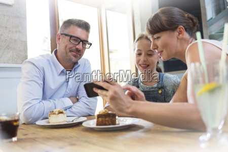 family with cell phone eating dessert