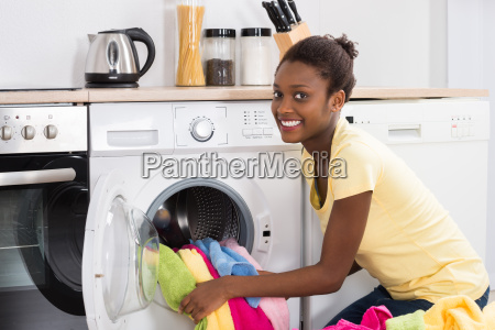woman putting clothes into washing machine