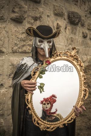 man with venetian bird mask holding