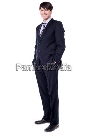 elegant businessman stood with hands in