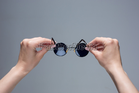 the female hands holding sunglasses on
