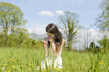 young woman sneezes on a flower