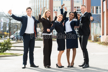 happy businesspeople in front building