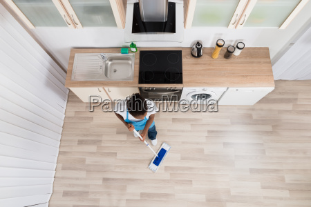 female janitor cleaning floor in kitchen