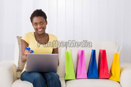 happy woman shopping online using laptop