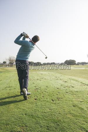 golfer hitting a golf ball on