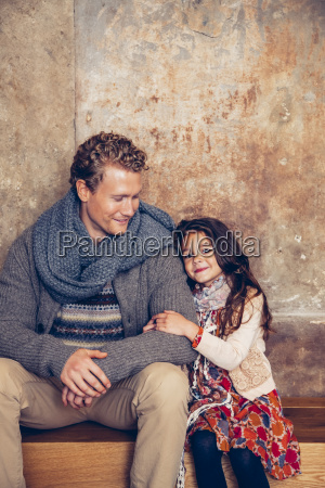 smiling father and daughter sitting on