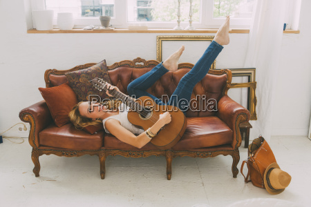 happy woman lying on leather couch