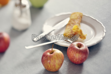 rolled pancake on plate and apples