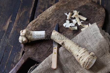 cut and peeled horseradish on wooden