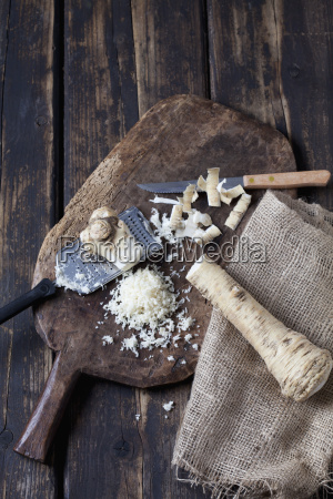 peeled and grated horseradish on wooden