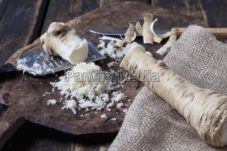 grated horseradish on wooden board
