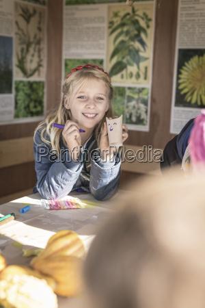 girl tinkering paper bats