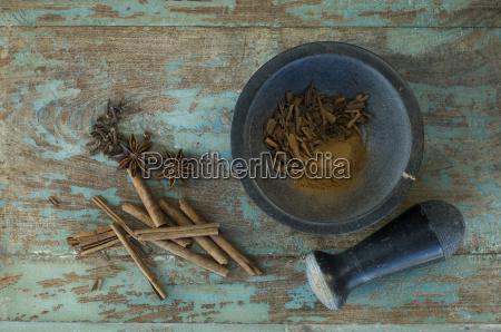 christmas spices and mortar on wood