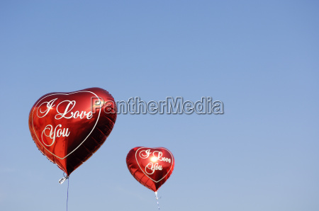 two red heart shaped balloons in