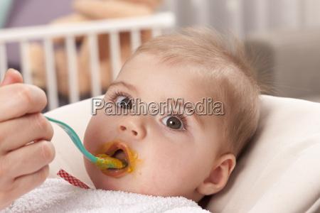 portrait of baby girl feeding by