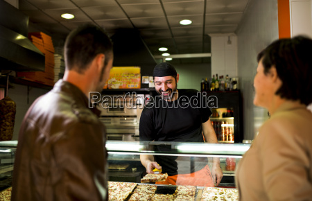 couple choosing piece of pizza at