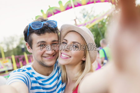 happy couple at fun fair taking