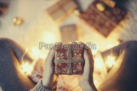 womans hands holding christmas present