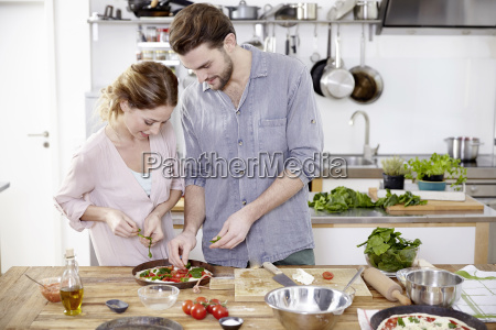 couple preparing pizza in kitchen
