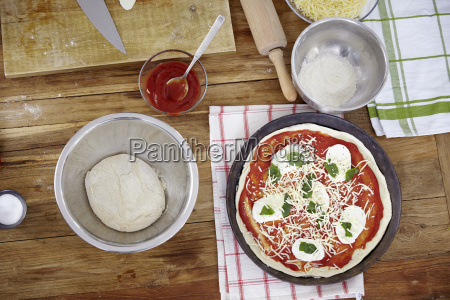 preparing pizza in kitchen