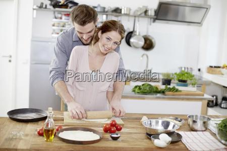 affectionate couple preparing pizza dough in