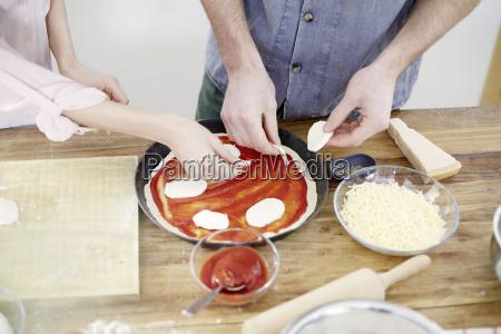 couple preparing pizza in kitchen