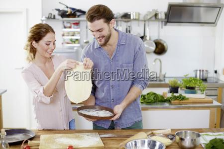 couple preparing pizza dough in kitchen