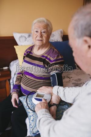 senior man checking blood pressure of