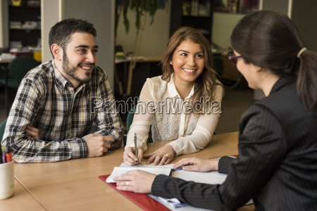 consultant helping young couple with documents