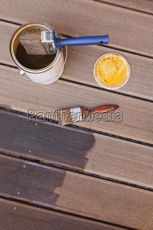 applying glaze with brush on floorboards