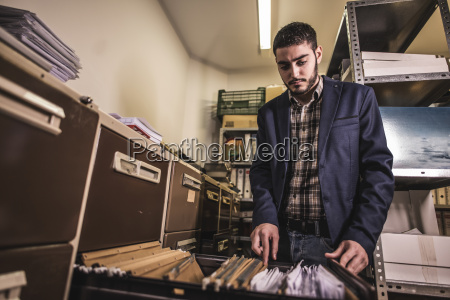 man searching for files at basement